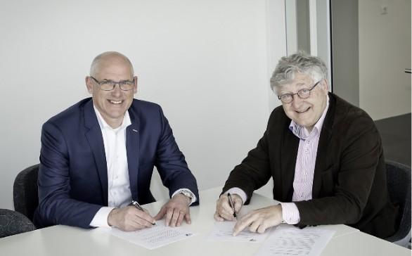 Ton Claassen, bestuurslid van de SKU (links) en de programmamanager van het vakexamen, Frank van den Boogaard, ondertekenen de samenwerkingsovereenkomst.
